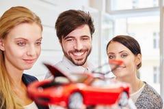 Les gens d'affaires contemplent un modèle de voiture images libres de droits