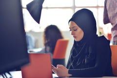 Les gens d'affaires contemporains multiraciaux se sont reliés aux dispositifs technologiques comme le comprimé et l'ordinateur po Image libre de droits