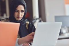 Les gens d'affaires contemporains multiraciaux se sont reliés aux dispositifs technologiques comme le comprimé et l'ordinateur po Photos libres de droits