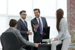 Les gens d'affaires discutant au-dessus des affaires nouvelles projettent dans le bureau Image libre de droits