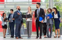 Les gens d'affaires groupent discuter le plan de projet de document communiquant, sourire parlant dans le bureau moderne Photographie stock