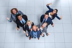 Les gens d'affaires groupent le sourire heureux se tenant à la vue supérieure de bureau moderne Photos stock