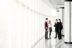 Les gens d'affaires marchent dans le hall de bureau sur le fond de fenêtre Images stock