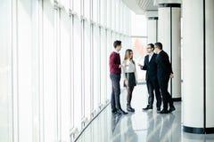 Les gens d'affaires marchent dans le hall de bureau sur le fond de fenêtre Photo stock