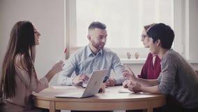 Les gens d'affaires multi-ethniques heureux font un brainstorm ensemble par la table en atmosphère amicale de lieu de travail sai banque de vidéos