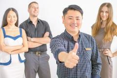 Les gens d'affaires réussis multiraciaux avec des pouces lèvent le geste Image stock