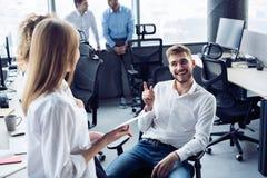 Les gens d'affaires r?ussis sont parlants et souriants pendant la pause-caf? dans le bureau images stock