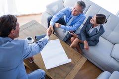 Les gens d'affaires se serrent la main sur le divan Image stock