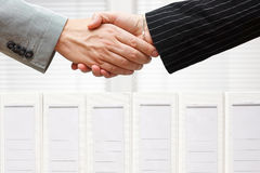 Les gens d'affaires sont poignée de main au-dessus des reliures, affaires et accou Photo stock