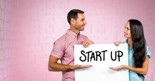 Les gens d'affaires tenant le panneau d'affichage avec commencent le texte là-dessus Photo libre de droits