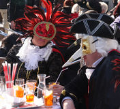 Les gens dans des costumes et les masques ayant des boissons au carnaval de Venise Image libre de droits