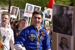 Les gens dans des costumes nationaux à la victoire défilent Photographie stock