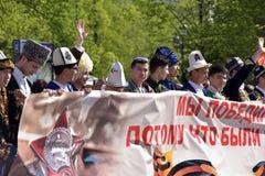 Les gens dans des costumes nationaux à la victoire défilent Photos stock
