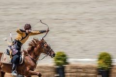 les gens dans des costumes des soldats antiques d'archer d'empire de tabouret tirant à la concurrence de tir à l'arc Photos stock