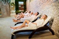Les gens dans des peignoirs se reposent dans le salon de station thermale Photo libre de droits