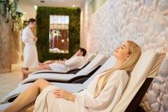 Les gens dans des peignoirs se reposent dans le salon de station thermale Image libre de droits