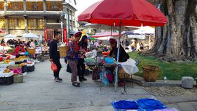 Les gens dans des vêtements traditionnels au marché d'un village de Yunnan, Chine photos stock