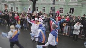 Les gens dans l'uniforme donnent cinq au porteur de flambeau Course de relais de flamme olympique de Sotchi dans le St Petersbour banque de vidéos