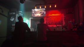 Les gens dans la barre jouent dans le jeu d'ordinateur et boivent de la bière clips vidéos