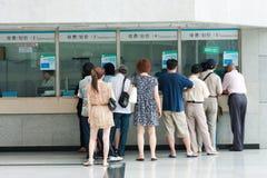 Les gens dans la file d'attente aux hublots de l'hôpital Photo stock