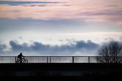 Les gens dans la position de silhouette sur un pont au-dessus d'une mer images stock