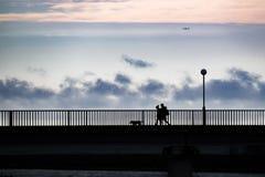 Les gens dans la position de silhouette sur un pont au-dessus d'une mer image stock