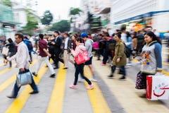 Les gens dans la tache floue de mouvement traversant une rue en Hong Kong Images stock