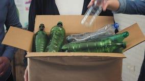 Les gens dans le bureau mettant les déchets en plastique dans le bac de recyclage clips vidéos