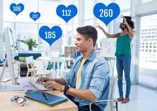 Les gens dans le bureau sur l'ordinateur avec des goûts dans des icônes de coeur Photos stock