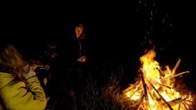 Les gens dans le camp chauffent par le feu banque de vidéos