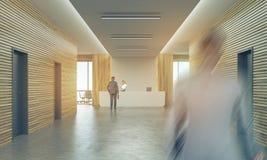 Les gens dans le couloir ensoleillé de bureau avec le compteur de réception Photo stock