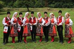 Les gens dans le folklore authentique traditionnel costument un pré près de Vratsa, Bulgarie images stock