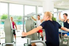Les gens dans le gymnase de sport sur la machine de forme physique Photos stock