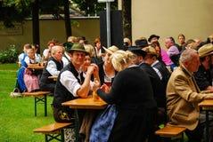 Les gens dans le vêtement bavarois tipical s'asseyent pendant un événement Images stock