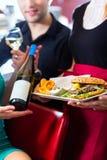 Les gens dans le wagon-restaurant américain ou le restaurant avec du vin Photographie stock libre de droits