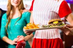 Les gens dans le wagon-restaurant ou le restaurant américain et la serveuse Images stock