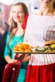 Les gens dans le wagon-restaurant ou le restaurant américain et la serveuse Image libre de droits