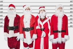 Les gens dans Santa costument la position côte à côte contre la ligne de police Photographie stock