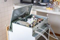 Les gens dans les travaux de technicien Un lave-vaisselle int?gr? cass? dans une cuisine blanche a ?t? enlev? de la kitchenette a image libre de droits