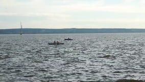 Les gens dans un bateau flottant sur le lac banque de vidéos