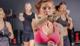Les gens dans un poinçon de formation de classe de boxe Photographie stock libre de droits