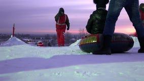Les gens dans une file d'attente et une tuyauterie de tour sur la neige et la glace inclinent clips vidéos