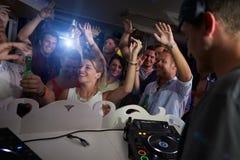 Les gens dansant dans la boîte de nuit avec le DJ dans le premier plan Photographie stock