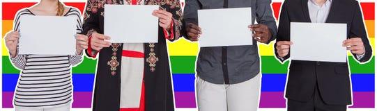 Les gens de différentes nationalités tiennent les feuilles vides dans la perspective du drapeau de LGBT Le concept de Photo libre de droits
