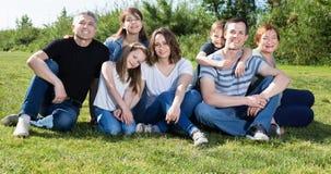 Les gens de différents âges prenant des photos sur la pelouse photos stock