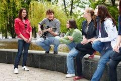 Les gens de groupe avec la guitare en stationnement de ville écoutent musique Photo stock