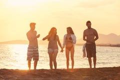 Les gens de plain-pied sur la belle plage dans le coucher du soleil d'été Images libres de droits