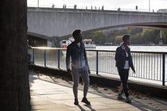Les gens descendant la rue pendant l'heure de pointe La rivière de montre de deux amis apprivoise photos stock