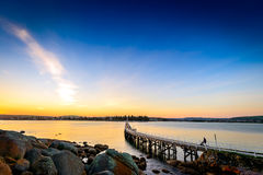 Les gens descendant le pont de pied au coucher du soleil, Victor Harbor, SA Photographie stock libre de droits