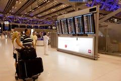 Les gens devant le panneau de déviations de l'aéroport Images libres de droits